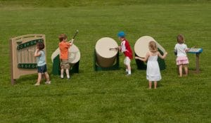 Children playing outdoor drums, xylophone, and chime panel on the playground