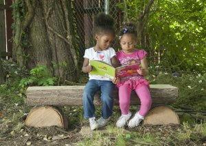 reading a book on half slab log bench