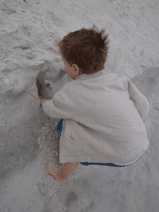child digging a hole in the sand