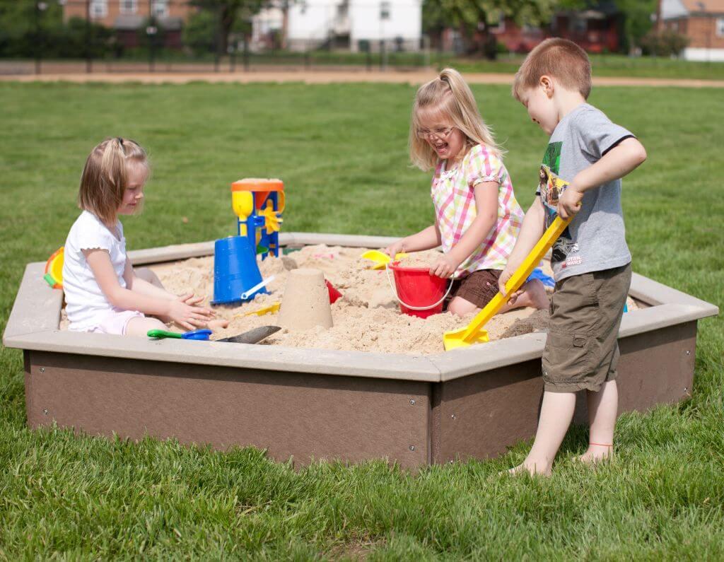 Children playing in outdoor sandbox