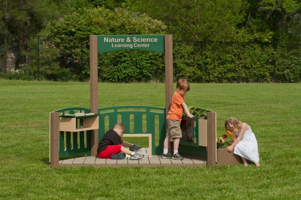 Children playing with Nature and Science Learning Center in the outdoor classroom