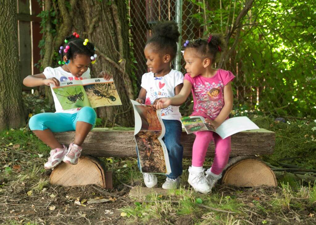 Children sitting on log bench in nature reading about insects