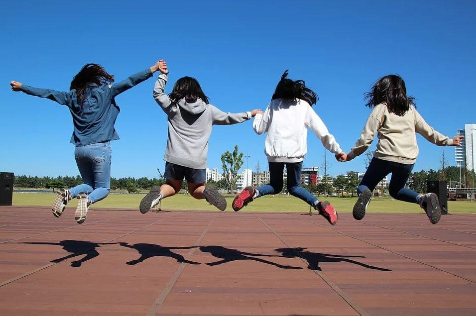 Four girls jumping in the air outside