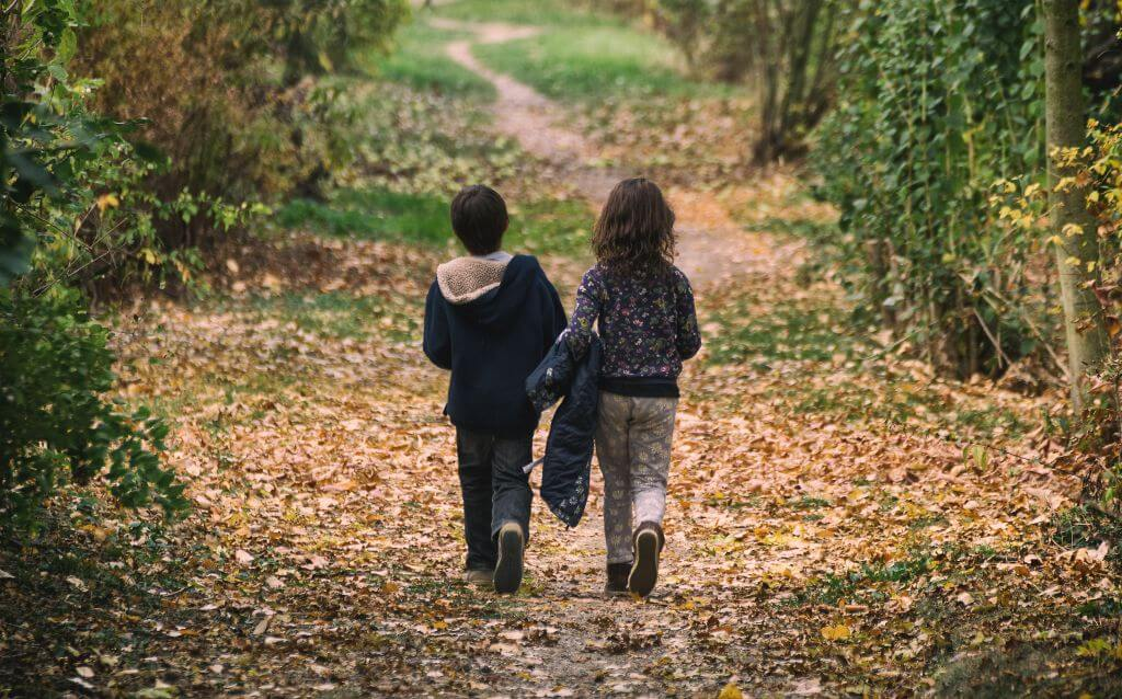 two children walking in the leaves in the woods