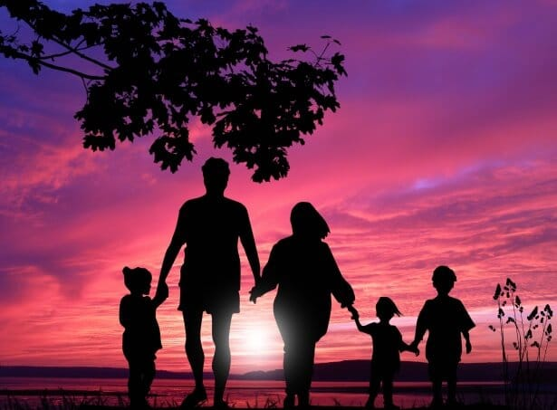 Family walking toward sunset