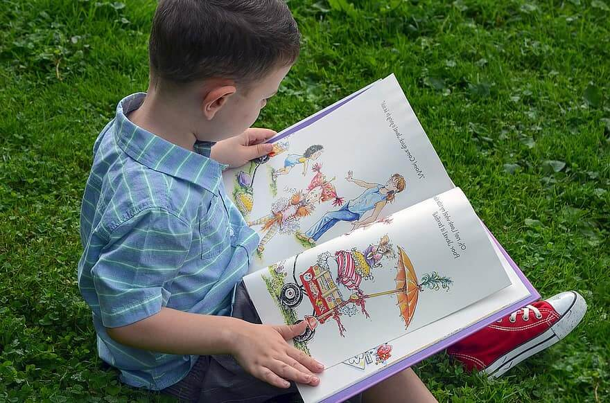 Young boy reading a book outside