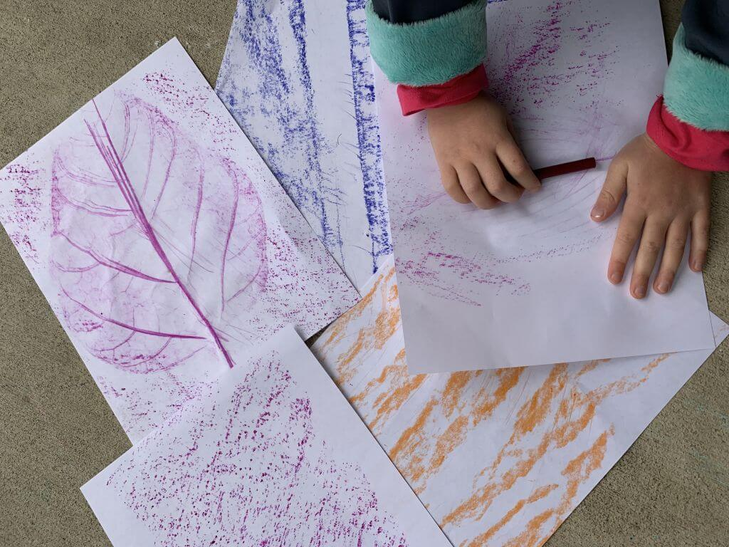 Child doing outdoor nature crayon rubbings